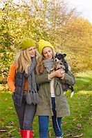Mother and Daughter Walking in Park Carrying Dog Stock Photo - Premium Rights-Managednull, Code: 822-06702249