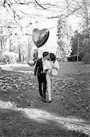 Young Couple Kissing in Park Holding Heart Shaped Balloons Stock Photo - Premium Rights-Managednull, Code: 822-06702464