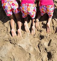 Back View of Girls in Matching Outfit Kneeling on Sand, Cropped Stock Photo - Premium Rights-Managednull, Code: 822-06702491