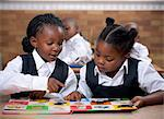 Young African schoolgirls looking through a picture book in class Stock Photo - Premium Royalty-Free, Artist: Mark Peter Drolet, Code: 6110-06702599