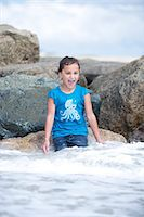 Girl Sitting on Rocks Playing in Sea Waves Stock Photo - Premium Rights-Managednull, Code: 822-06702505