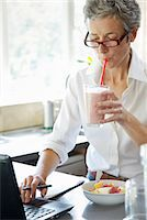 Woman Drinking Smoothie whilst Typing on Laptop Stock Photo - Premium Rights-Managednull, Code: 822-06702506