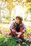 Young Man Sitting in Park in Autumn Stock Photo - Premium Rights-Managed, Artist: ableimages, Code: 822-06702537
