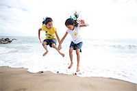 Twin Girls Jumping Over Waves Stock Photo - Premium Rights-Managednull, Code: 822-06702560