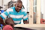 African father and son making measurements in a workshop Stock Photo - Premium Royalty-Free, Artist: Yuri_Arcurs                   , Code: 6110-06702616