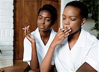 Two African teenage girls sit outside smoking cigarettes Stock Photo - Premium Royalty-Freenull, Code: 6110-06702679