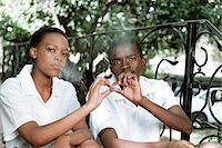 Two African teenagers sit together outside, smoking cigarettes Stock Photo - Premium Royalty-Freenull, Code: 6110-06702683