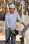 Chinese man refuelling his car at the gas station Stock Photo - Premium Royalty-Free, Artist: Cultura RM, Code: 6105-06702871