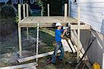Carpenter using nail gun to install deck joists on home Stock Photo - Premium Royalty-Freenull, Code: 6105-06702899