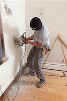 Hispanic carpenter using circular saw to cut wallboard for deck doorway in house Stock Photo - Premium Royalty-Freenull, Code: 6105-06702938