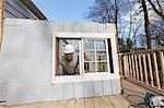 Hispanic carpenter removing newly cut door access to deck on home Stock Photo - Premium Royalty-Freenull, Code: 6105-06702955