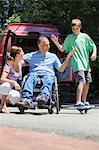 Man with spinal cord injury in wheelchair giving high-five to son on skateboard Stock Photo - Premium Royalty-Free, Artist: Pierre Arsenault, Code: 6105-06703000