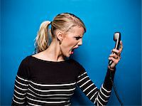 Young Woman Screaming at Telephone, Studio Shot Stock Photo - Premium Royalty-Freenull, Code: 600-06714008