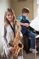 Smiling girl playing saxophone Stock Photo - Premium Royalty-Freenull, Code: 649-06716492