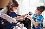 Boy helping girl play guitar Stock Photo - Premium Royalty-Free, Artist: Blend Images, Code: 649-06716501