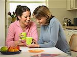 Women having coffee together in kitchen Stock Photo - Premium Royalty-Free, Artist: Blend Images, Code: 649-06716579