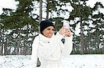 Woman taking picture in snowy forest Stock Photo - Premium Royalty-Free, Artist: Michael Mahovlich, Code: 649-06716643