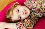 Smiling girl laying on pillow Stock Photo - Premium Royalty-Freenull, Code: 649-06716801