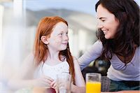 Mother smiling at daughter at breakfast Stock Photo - Premium Royalty-Freenull, Code: 649-06716963