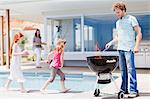 Girls around pool as father grills Stock Photo - Premium Royalty-Free, Artist: Cultura RM, Code: 649-06716985
