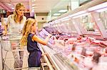 Mother and daughter at butcher counter Stock Photo - Premium Royalty-Free, Artist: Blend Images, Code: 649-06717221