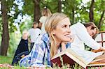 Woman reading on blanket in park Stock Photo - Premium Royalty-Free, Artist: Blend Images, Code: 649-06717239