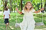Girl playing on swing in park Stock Photo - Premium Royalty-Freenull, Code: 649-06717240