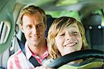 Boy driving car on fathers lap Stock Photo - Premium Royalty-Free, Artist: Westend61, Code: 649-06717293