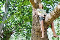 Smiling boy sitting in tree Stock Photo - Premium Royalty-Freenull, Code: 649-06717299