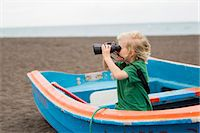 side view of person rowing in boat - Boy using binoculars on beach Stock Photo - Premium Royalty-Freenull, Code: 649-06717317