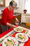 Older woman plating dinner in kitchen Stock Photo - Premium Royalty-Freenull, Code: 649-06717345
