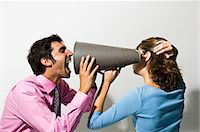 Businessman shouting into colleagues ear Stock Photo - Premium Royalty-Freenull, Code: 649-06717404