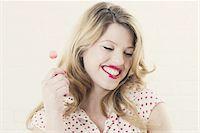 Smiling woman eating lollipop Stock Photo - Premium Royalty-Freenull, Code: 649-06717608