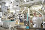 Worker with machinery in biscuit factory Stock Photo - Premium Royalty-Free, Artist: Blend Images, Code: 649-06717699