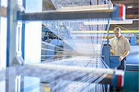 production - Worker examining loom in textile mill Stock Photo - Premium Royalty-Freenull, Code: 649-06717736