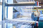 Worker examining loom in textile mill Stock Photo - Premium Royalty-Free, Artist: Westend61, Code: 649-06717737