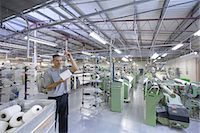 Worker examining thread in textile mill Stock Photo - Premium Royalty-Freenull, Code: 649-06717757