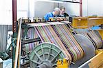 Worker using looms in textile mill Stock Photo - Premium Royalty-Free, Artist: Blend Images, Code: 649-06717767