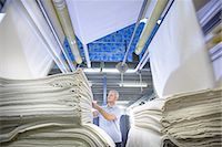 Worker examining fabric in textile mill Stock Photo - Premium Royalty-Freenull, Code: 649-06717793