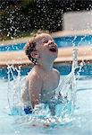 Boy splashing in swimming pool Stock Photo - Premium Royalty-Free, Artist: Blend Images, Code: 649-06717797