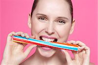 Smiling woman biting candy Stock Photo - Premium Royalty-Freenull, Code: 649-06717827