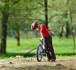 Boy climbing on bicycle in park Stock Photo - Premium Royalty-Free, Artist: Raymond Forbes, Code: 649-06717911