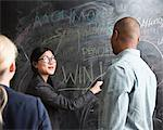 Woman writing on blackboard, colleagues watching Stock Photo - Premium Royalty-Free, Artist: Ikon Images, Code: 614-06718115