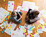 Colleagues sitting cross legged on floor with papers and adhesive notes Stock Photo - Premium Royalty-Free, Artist: Westend61, Code: 614-06718144