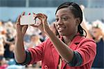 Woman in stadium, recording event with her phone Stock Photo - Premium Royalty-Free, Artist: Blend Images, Code: 614-06718196