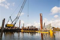 Crane at construction site on water Stock Photo - Premium Royalty-Freenull, Code: 614-06718256