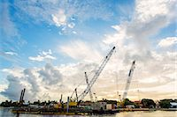 Construction cranes on waterfront Stock Photo - Premium Royalty-Freenull, Code: 614-06718262
