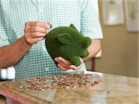 Man putting coins in green piggy bank Stock Photo - Premium Royalty-Freenull, Code: 614-06718880