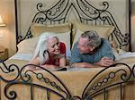 Older couple reading on bed Stock Photo - Premium Royalty-Free, Artist: Westend61, Code: 614-06718894