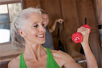 Older woman lifting weights at home Stock Photo - Premium Royalty-Freenull, Code: 614-06718930